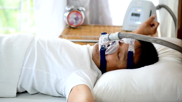 Sleep apnea therapy,man wearing CPAP mask wake up in the morning video