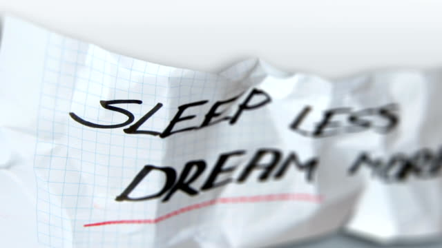 Sleep less and dream more words on torn paper video