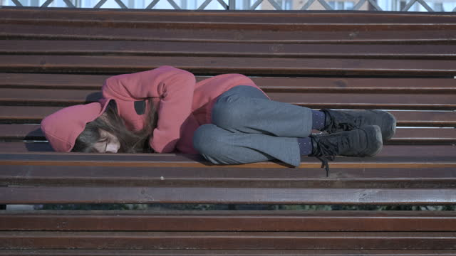 Sleep on the bench. Sleep on the bench. A view of an alone child sleeping on the bench in the park. homelessness stock videos & royalty-free footage