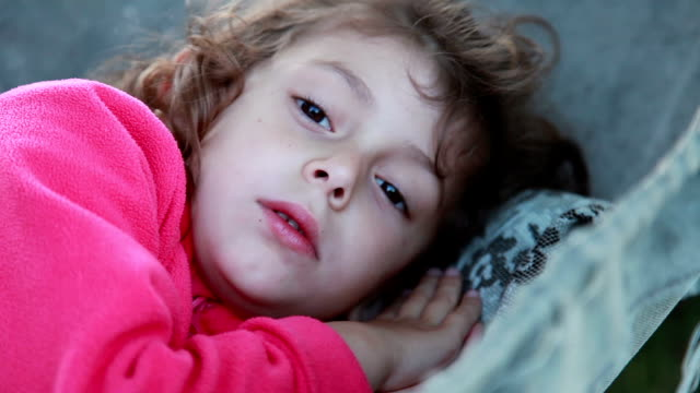 Video Sleeping little girl wakes up and looks at camera
