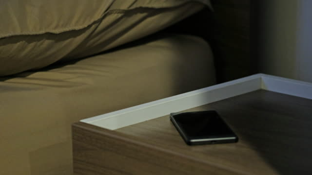 vídeos de stock e filmes b-roll de sleeping man on bed awakened by smart phone incoming call at night - table