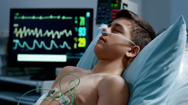 Sleeping patient and heart monitor Rack focus shot from sleeping teenage patient to heart monitor medical oxygen equipment stock videos & royalty-free footage