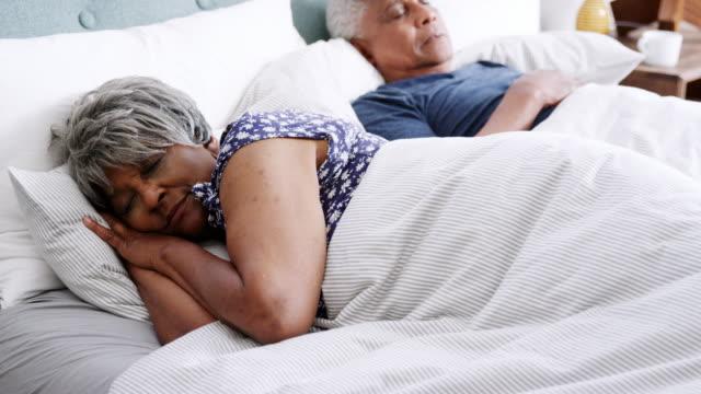vídeos y material grabado en eventos de stock de pareja senior dormir acostado en la cama juntos - filmada en cámara lenta - dormir