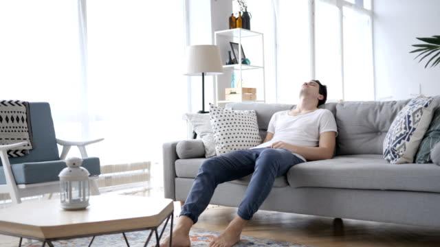 vídeos de stock e filmes b-roll de sleeping tired young man on sofa at home - lento