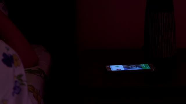 stockvideo's en b-roll-footage met slapende vrouw op bed gewekt door slimme telefoon inkomende oproep 's nachts - alarm, home,