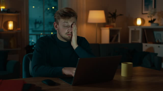 sleepy and exhausted man works on a laptop while sitting at his desk at home in the middle of the night. - работа допоздна стоковые видео и кадры b-roll