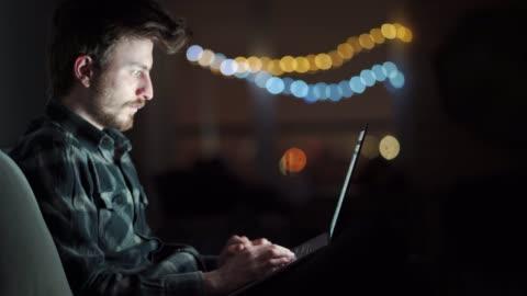 半夜, 昏昏欲睡、疲憊的男人坐在家裡的沙發上, 在筆記本電腦上工作。年輕的男生晚上在電腦上工作到很晚。 - laptop 個影片檔及 b 捲影像