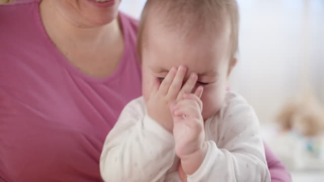 Sleepy baby boy sitting in his mother's lap Medium handheld shot of a sleepy baby boy being held by his mother in her lap. Shot in Slovenia. sleeve stock videos & royalty-free footage