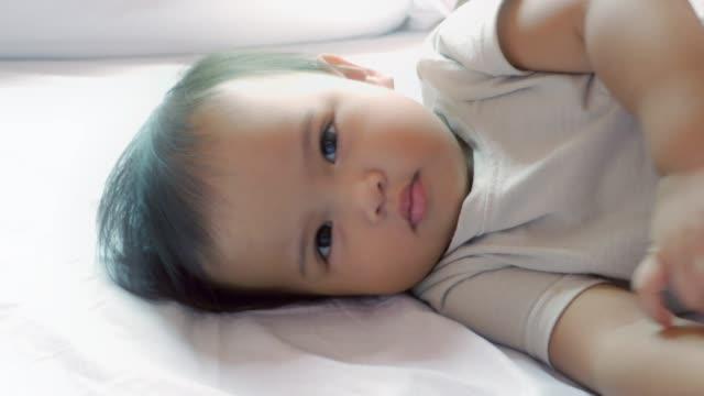 Sleepy baby lying on the white bed