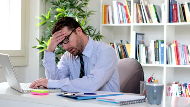 sleepy businessman sitting behind his office desk - uomo stanco video stock e b–roll