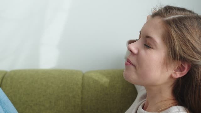 Sleepy caucasian woman taking a rest on the couch close up video