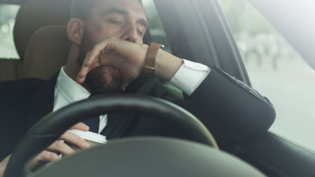 sleepy, drowsy businessman driving a car - усталый стоковые видео и кадры b-roll