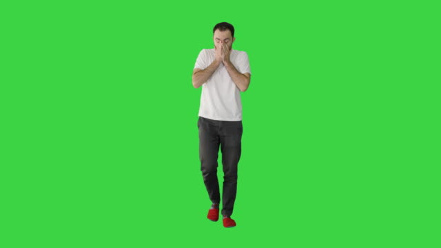 Sleepy male in white t-shirt yawning and rubbing eyes while walking on a Green Screen, Chroma Key