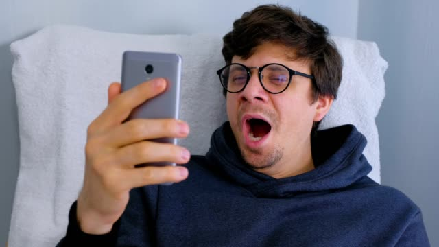 Sleepy man in glasses yawns and browsing in social media on smartphone sitting in armchair. video