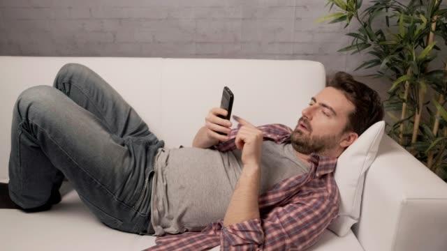 vídeos de stock e filmes b-roll de sleepy man using smartphone on the couch - lento