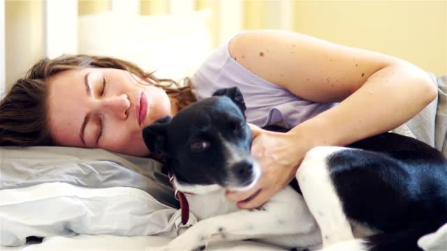 vidéos et rushes de femme souriante somnolente et son chien dans le lit. hd - femme seule s'enlacer