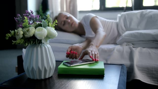 sleepy woman turning off mobile alarm clock - sonnecchiare video stock e b–roll