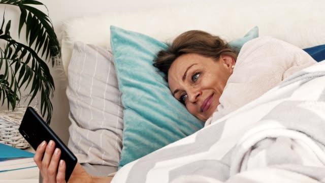 Sleepy woman using phone in bed