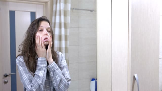 Sleepy woman with hangover in the bathroom looking at her reflection in the mirror. video