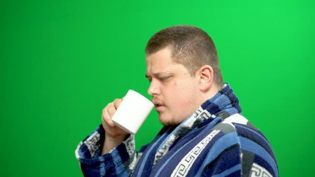 vidéos et rushes de un jeune homme endormi. bâillements. il boit le thé du matin. veut dormir. - peignoir