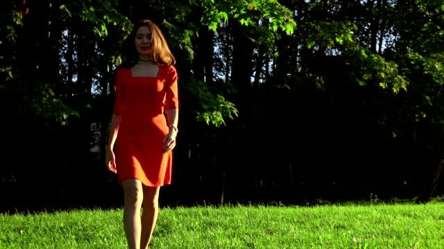 kırmızı elbise parkta çim yürüyüş ince esmer kız. yavaş hareket video, 120 fps - uzun adımlarla yürümek stok videoları ve detay görüntü çekimi
