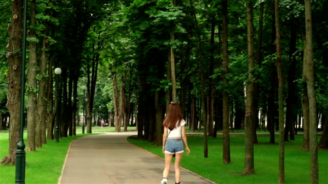 slender girl in denim shorts summer rollerblading slender girl in denim shorts summer rollerblading in the Park charming stock videos & royalty-free footage