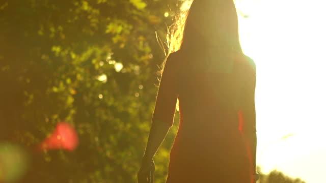 parkta güneşe karşı yürüyüş ince kız siluet. yavaş hareket video, 120 fps - uzun adımlarla yürümek stok videoları ve detay görüntü çekimi