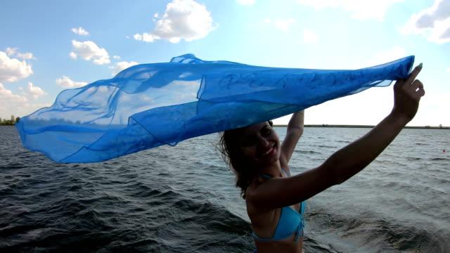 smal tjej med en stor halsduk på stranden. - sarong bildbanksvideor och videomaterial från bakom kulisserna