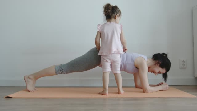 vídeos de stock e filmes b-roll de yoga: slender mom doing plank exercise while her little daughter playing with her at home- front view - treino em casa