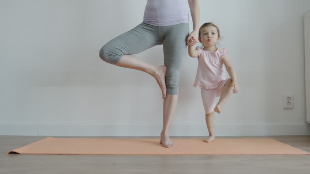 YOGA: Slender mom with her pretty little daughter practising yoga on a mat at home - Front View