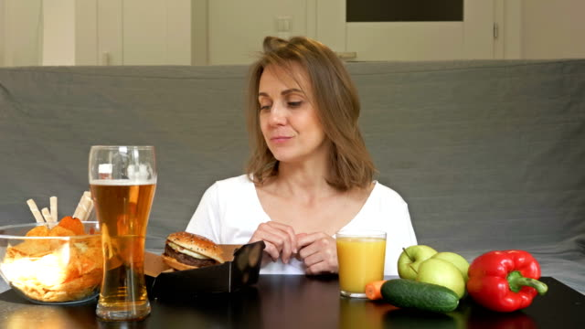 Slender pretty woman does not know what she prefers to eat. The difficulty of choosing between healthy and unhealthy diets