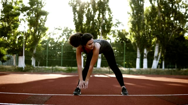 Slender sexy athlete performs slopes down in black legging. Exercises to strengthen the muscles of the hips and legs. Small outdoors stadium