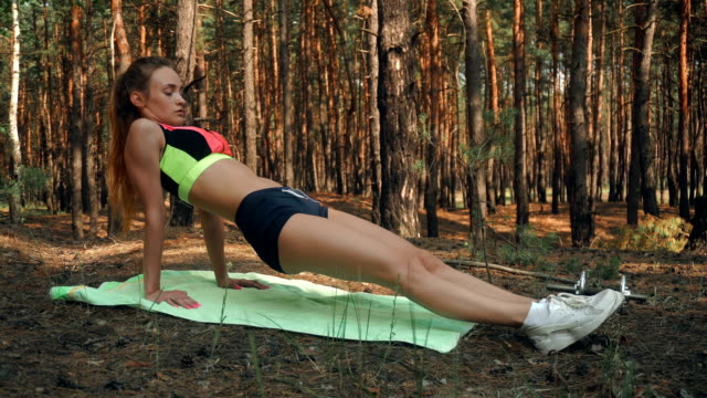slender sport girl with a ponytail in short shorts and a bright top stands on the hands video