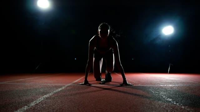 ağır çekimde yolda yastıkları yayınlanmaya başlaması için ince genç kız atlet durumdadır - başlama çizgisi stok videoları ve detay görüntü çekimi