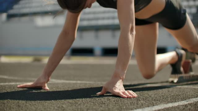 vidéos et rushes de slender jeune athlète fille est en position de commencer à courir dans les pads sur la piste au ralenti. - starting block