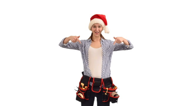 slender young woman construction worker in a cap of Santa Claus shows a copy space on a white background video