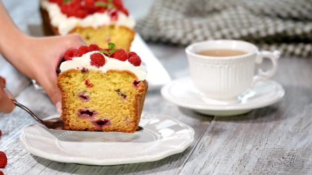 A Slice of berry cake with raspberries and lemon glaze.