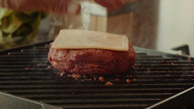 vídeos de stock e filmes b-roll de a slice of cheddar on plant based, non-meat, vegan burger that is cooked - meat texture