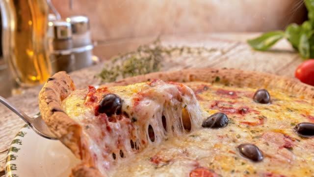 SLO MO DS スライス チーズのピザ板から持ち上げられているの ビデオ