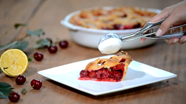 A slice of cherry pie with ice cream.