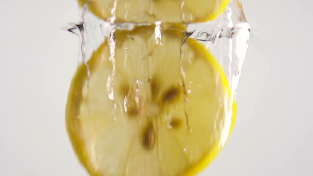 Slice Of Lemon Falling Slow Motion In Clear Water video