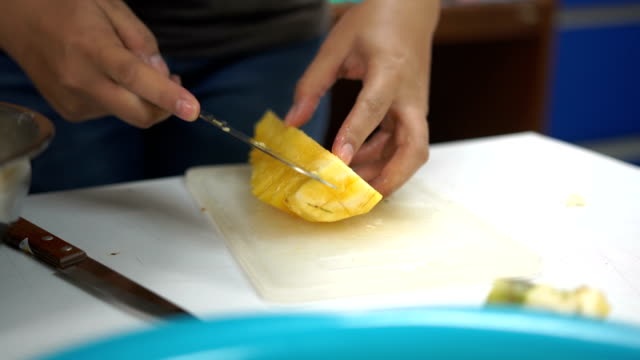 Slice pineapple to small pieces on a white table video