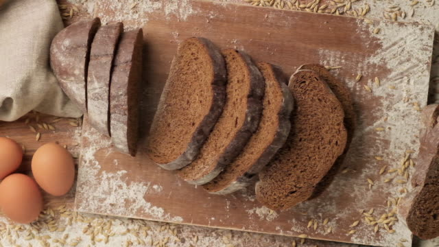 Sliced brown bread falling on table. Organic bread falling down. Food concept.