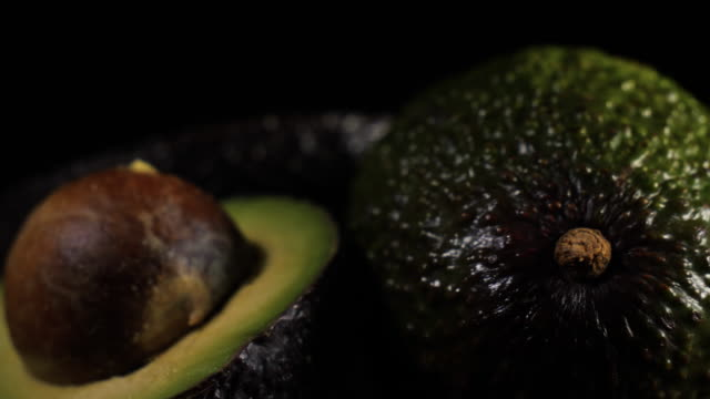 Sliced Half Avocados in Close Up rotating against black background in studio A fresh split avocado rotates against black background avocado stock videos & royalty-free footage