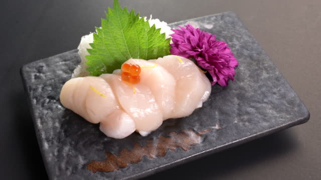 sliced japanese food scallop with salmon roe on top sashimi dinner meal on a turn table . - sashimi video stock e b–roll