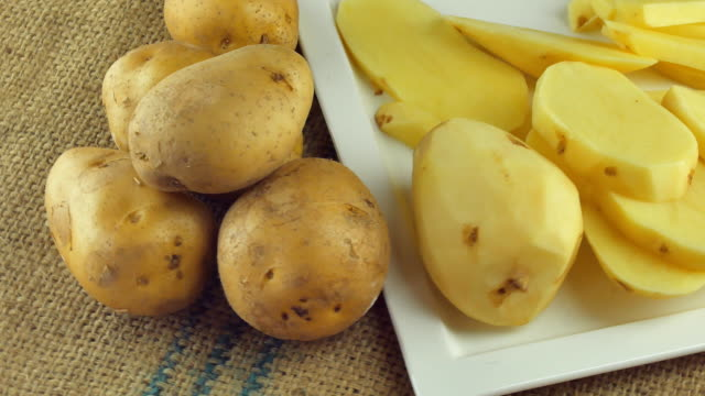 sliced potatoes and raw potatoes rotating - приготовленный картофель стоковые видео и кадры b-roll