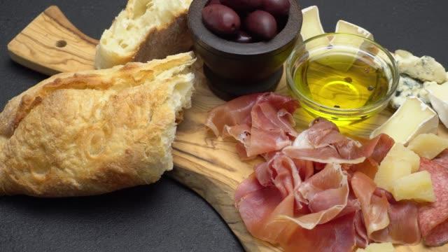 in scheiben geschnittenen schinken, käse und salami wurst auf einem holzbrett - brie stock-videos und b-roll-filmmaterial