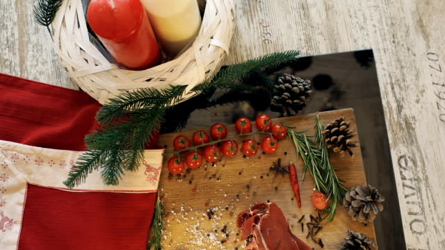 Sliced prosciutto lie on the wooden plate with salt, pepper, cherry potatos. Christmas atmosphere video