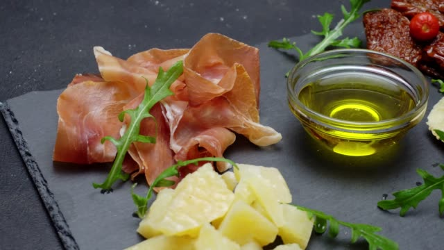 sliced prosciutto or jamon meat and cheese on concrete background video
