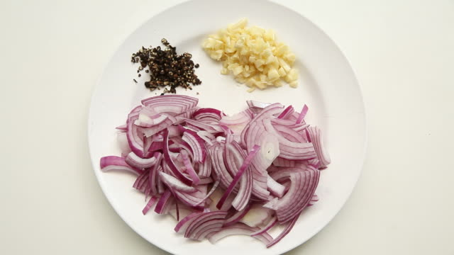 sliced red onion, chopped garlic and crushed black pepper in white plate on white background - aglio cipolla isolated video stock e b–roll